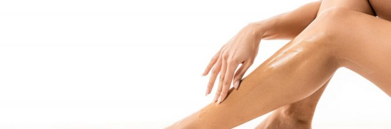 cropped shot of african american woman touching leg with sugar wax on white
