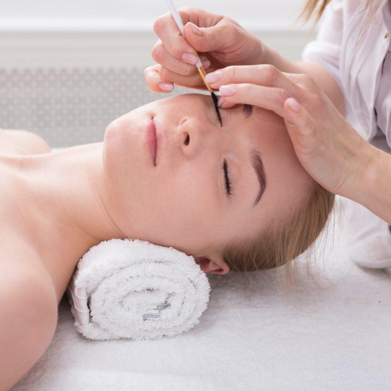 Woman gets eyelashes tinting by beautician at spa